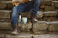 Young man sitting on steps having coffee break, partial view - EBSF000087