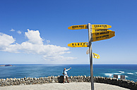 New Zealand, North Island, Man standing at view point with sign post at Cape Reinga - GW002655