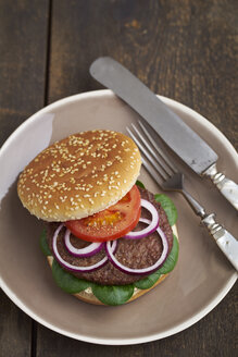 Burger with mincemeat, tomato, lamb's lettuce and red onions on plate - ECF000461
