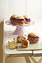 Mini-Burger with pulled pork, red cabbage and fried onions on cake stand and pretzel rolls on chopping board - ECF000447