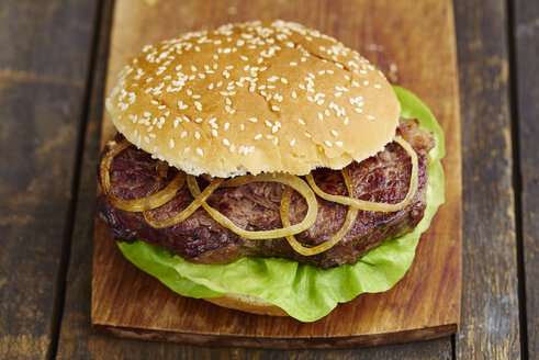 Steak-Burger with beefsteak, salad and fried onions on chopping board - ECF000449