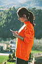 Young female jogger hearing music with smartphone - EBSF000092