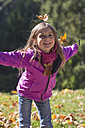 Portrait of little girl throwing autumn leaves in park - SARF000365