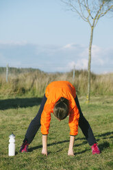 Young female jogger stretching on a meadow - EBSF000111