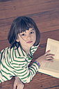 Portrait of little girl reading book at home - LVF000846