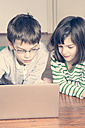 Portrait of brother and sister using laptop at home - LVF000843