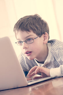Portrait of boy using laptop at home - LVF000893