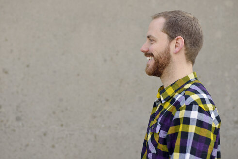 Profile of laughing young man wearing checkered shirt in front of grey wall - BR000155