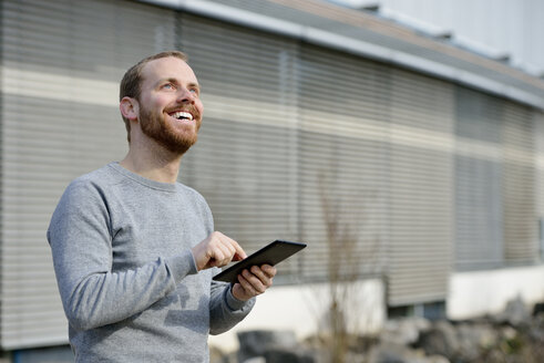 Portrait of happy young man with mini tablet - BR000149