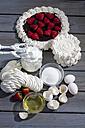 Meringues, meringue tart and meringue ingredients on grey wood - CSF021025