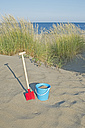 Italy, Adria, shovel and basket at beach dunes - ASF005284