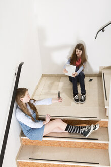 Two teenage girls sitting on stairs using smartphone and digital tablet - MAEF008278