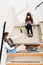 Two teenage girls sitting on stairs using smartphone and digital tablet - MAEF008279