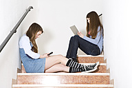 Two teenage girls sitting on stairs using smartphone and digital tablet - MAEF008281