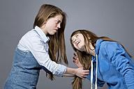 Teenage girl pulling her sisters hair - MAEF008291