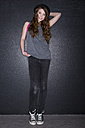 Portrait of teenage girl standing in front of dark wall - MAEF008259