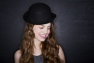 Portrait of teenage girl with bowler hat in front of dark wall - MAEF008260