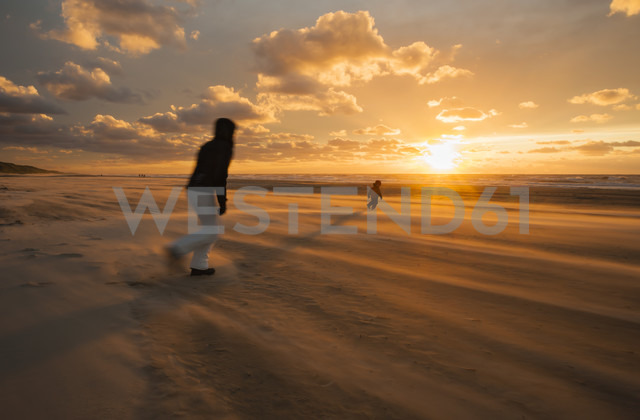 Denmark, Jutland, Lokken, mother trying to catch her child on stormy beach at sunset - JBF000072