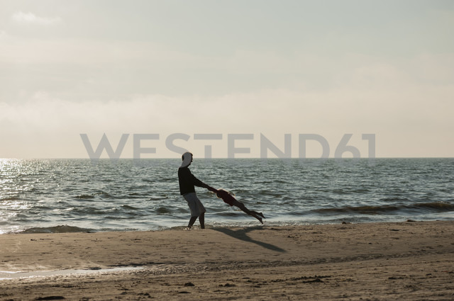 Denmark, Jutland, Lokken, father playing with daughter on beach - JBF000076