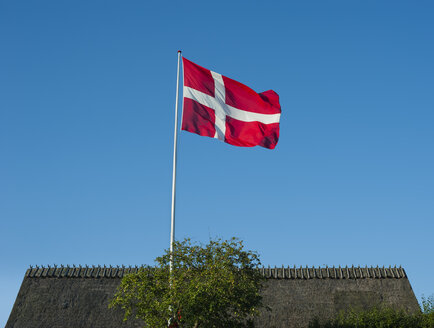 Denmark, Mon island, Danish flag, reed covered roof in the background - JBF000081