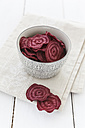 Bowl of beetroot chips on cloth and white wooden table - EVGF000448