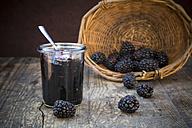 Basket of blackberries (Rubus sectio Rubus) and preserving jar of blackberriy jelly on wooden table - LVF000852
