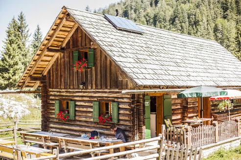 Austria, Gosau, man reading at alpine cabin - KVF000084