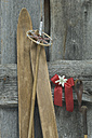 Old skis, ski pole, red bow with Edelweiss (Leontopodium alpinum) leaning at wooden wall - ASF005288