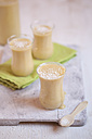 Glasses of mango smoothie with desiccated coconut on cloth and kitchen board - SBDF000660
