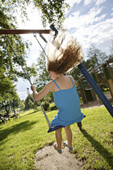Germany, Coburg, teenage girl on a swing in the park - VTF000179