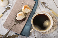 Two coco macaroons on cake server and cup of black coffee, elevated view - CSTF000185