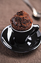 Black cup of chocolate cup cake and a tea spoon on brown cloth - MYF000240