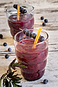 Two glasses of wild berry smoothie and  blueberries on wooden table - SARF000393