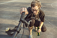 Germany, Hannover, Bike polo player checking bike - MUMF000074