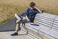 Germany, Baden-Wurttemberg, Teenage boy sitting on bench, learning - WDF002413