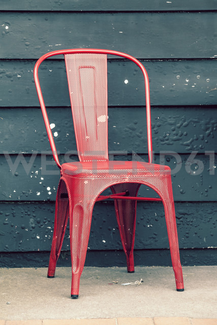 New Zealand, Ngatea, red metal chair in front of dark green facade - WV000507 - Valentin Weinhäupl/Westend61