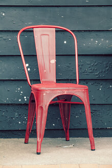 New Zealand, Ngatea, red metal chair in front of dark green facade - WV000507