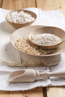 Bowls of puffed buckwheat, amaranth and quinoa on wooden board and kitchen towel - MYF000261
