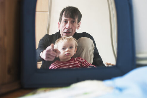 Germany, Father and son looking in mirror - MUF001469
