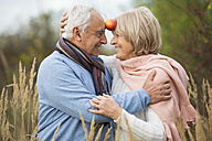Portrait of happy senior couple having fun with an apple - WESTF019206