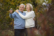Portrait of smiling senior couple taking self-portrait with smartphone - WESTF019212