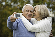 Portrait of happy senior couple taking self-portrait with smartphone - WESTF019215