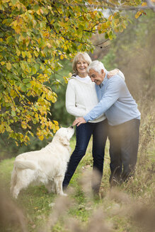 Portrait of happy senior couple with dog - WESTF019218