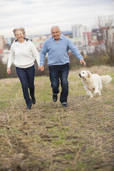 Smiling senior couple running hand in hand - WESTF019233