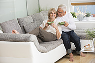 Senior couple with tea cups side by side on sofa in living room - WESTF019236