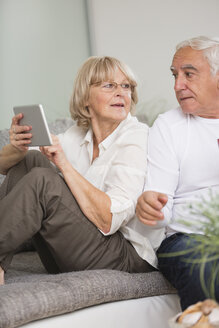 Senior couple with digital tablet side by side on sofa in living room - WESTF019242