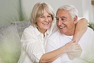 Happy senior couple together in living room - WESTF019245