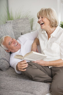 Laughing senior couple with book on sofa in living room - WESTF019248