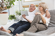 Senior couple with digital tablet side by side on sofa in living room - WESTF019257