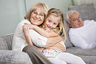 Portrait of senior woman hugging granddaughter on sofa in living room - WESTF019169